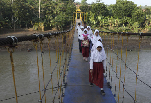 Students walk across a new bridge on their way to school at Sanghiang Tanjung village in Lebak regency